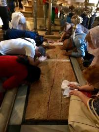Praying over slab where Jesus's body was laid.